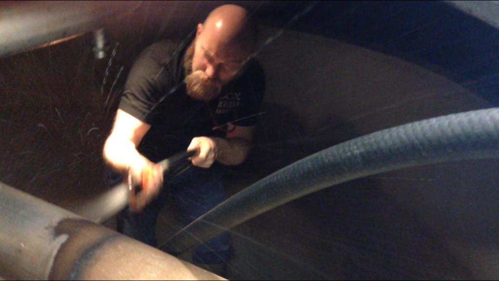 Martin tvättar insidan av ett jäskar (washback).