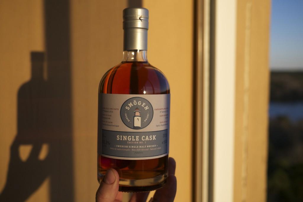 En flaska och en whiskybloggares vänsterhand i kvällsljuset på balkongen.
